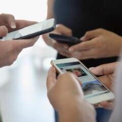 Drei Menschen halten Handys in den Händen