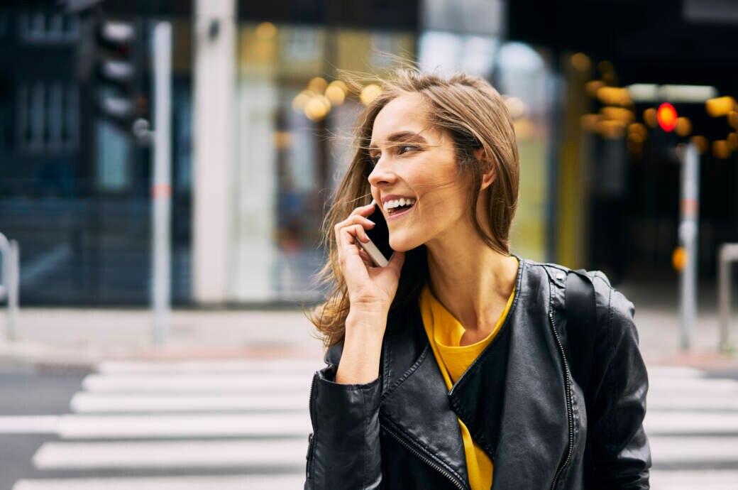 Rothaarige Frau telefoniert mit dem Handy auf der Straße