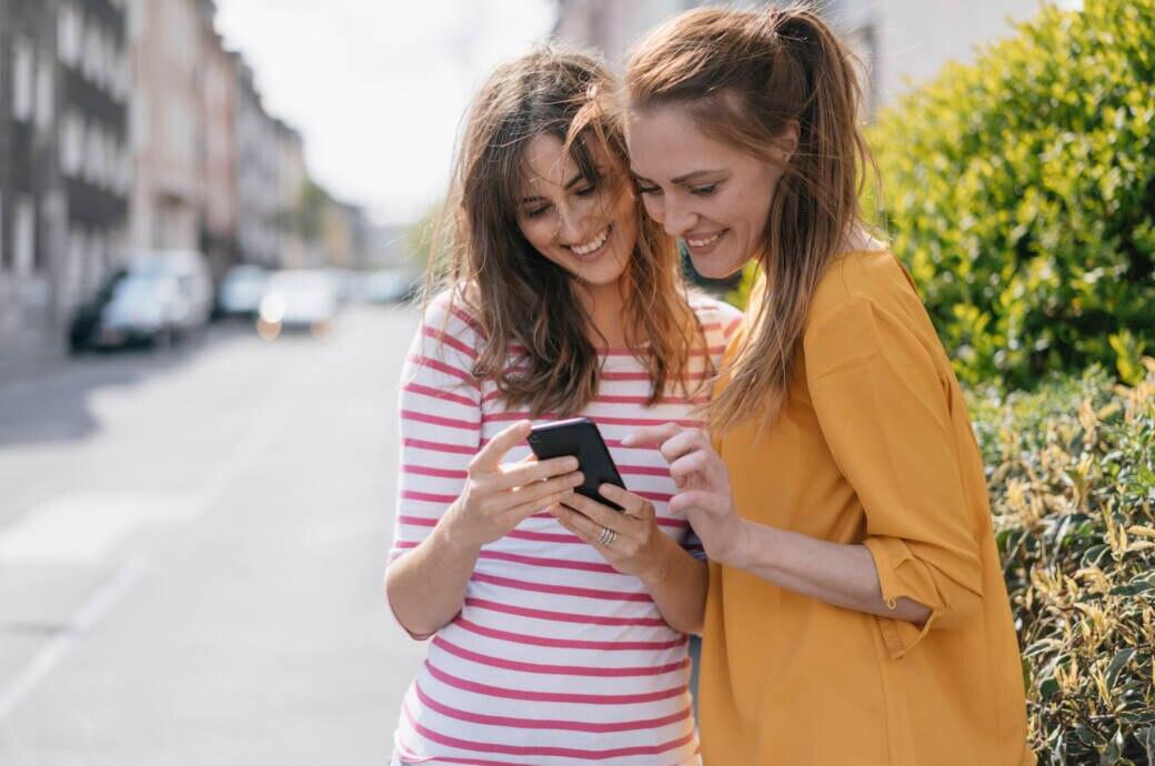 Zwei Frauen blicken auf der Straße auf ein Smartphone