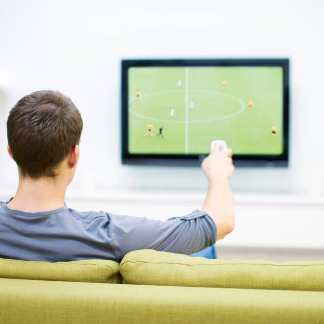 Mann schaut Fußball auf Fernseher