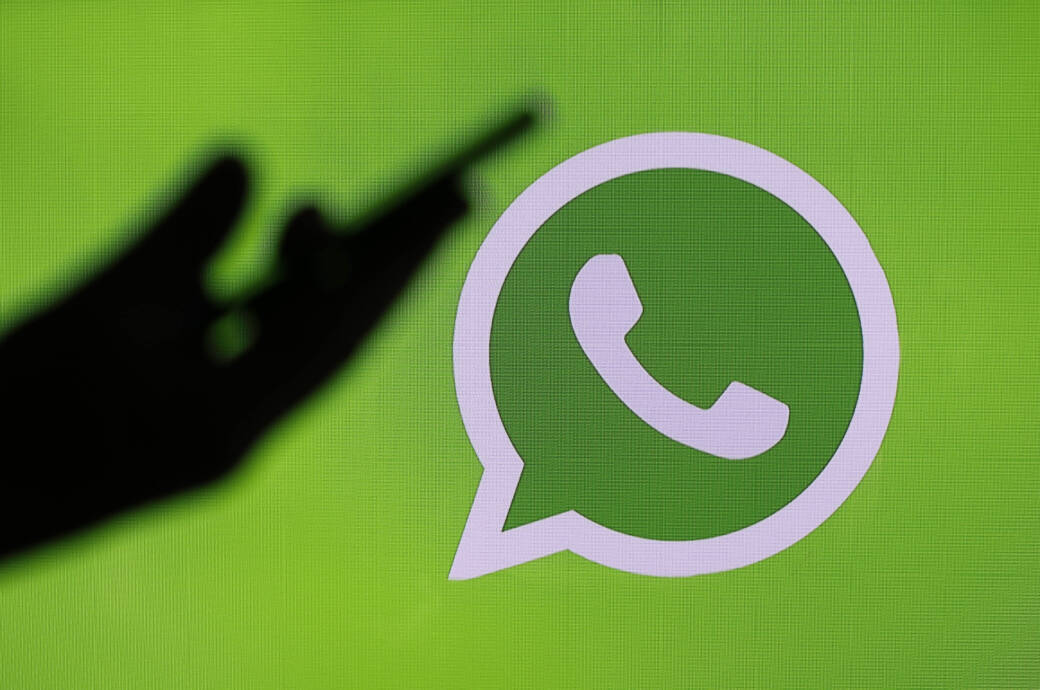 Logo von Whatsapp im Hintergrund, vorne ist eine Hand mit Smartphone zu sehen