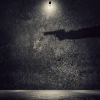 Schatten einer Hand mit Pistole an der Wand_ Sinnbild für Krimi-Serien auf Netflix