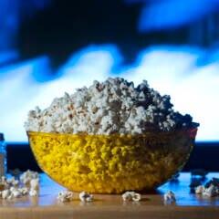 Die neuen Serien und Filme auf Sky: volle Popcornschale und Salzstreuer vor einem eingeschalteten Fernseher