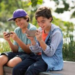 Zwei Jungen sitzen nebeneinander und spielen Spiele-Apps auf ihren Handys