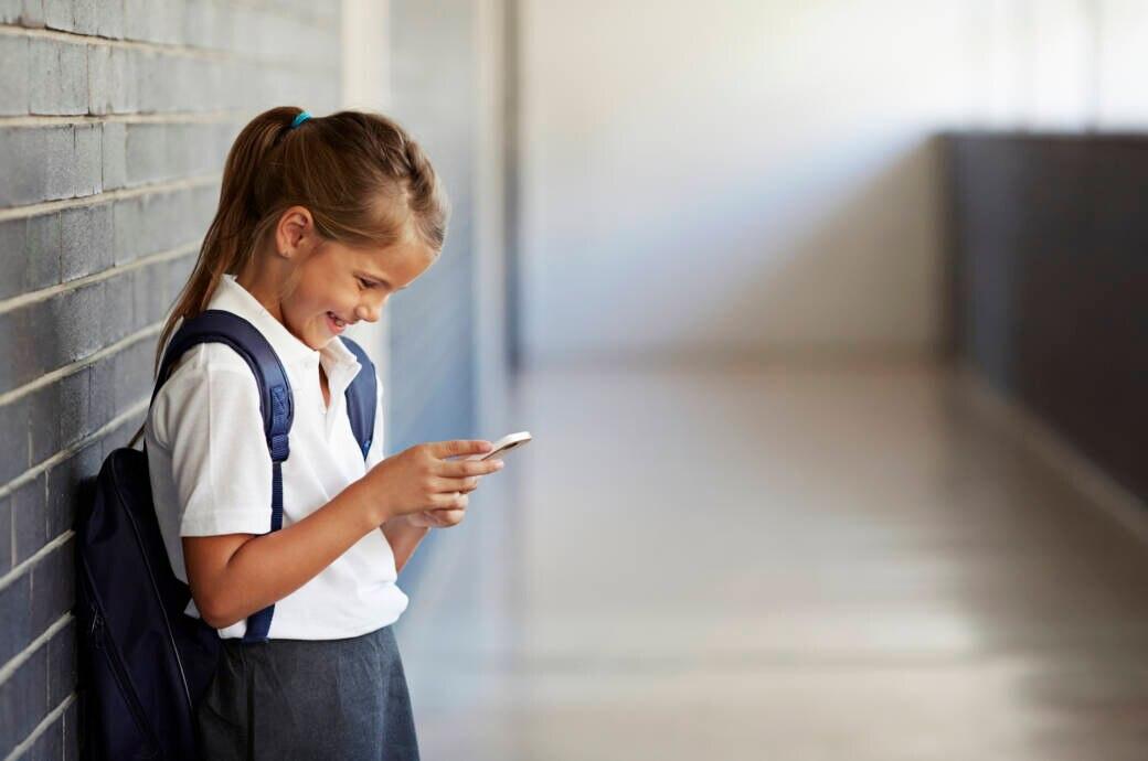 Kinderhandys werden relevanter: ein kleines Mädchen steht lächelnd mit Schulranzen im Gang und guckt auf ihr Handy
