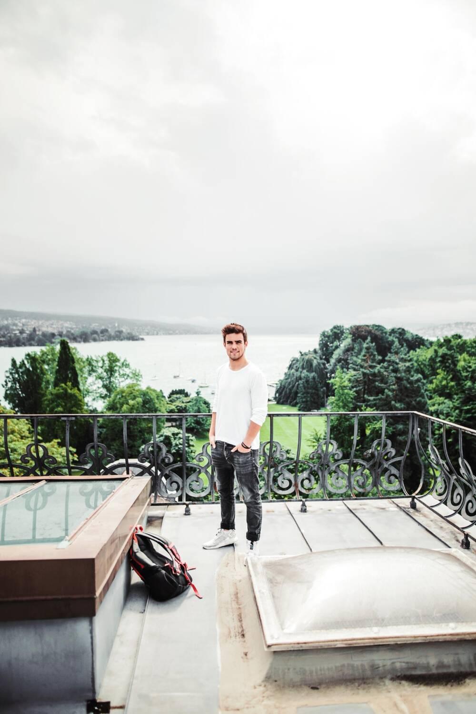 Rubin Lind steht auf einer Dachterrasse, vor ihm liegt sein Schulrucksack
