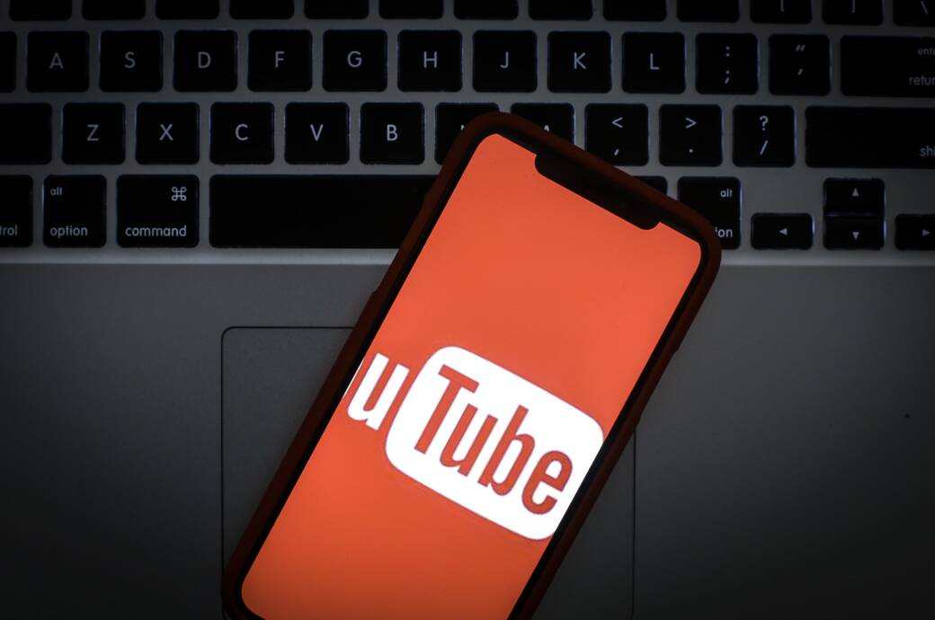 Das Logo von Youtube auf dem Display eines Smartphones vor einer Laptop-Tastatur
