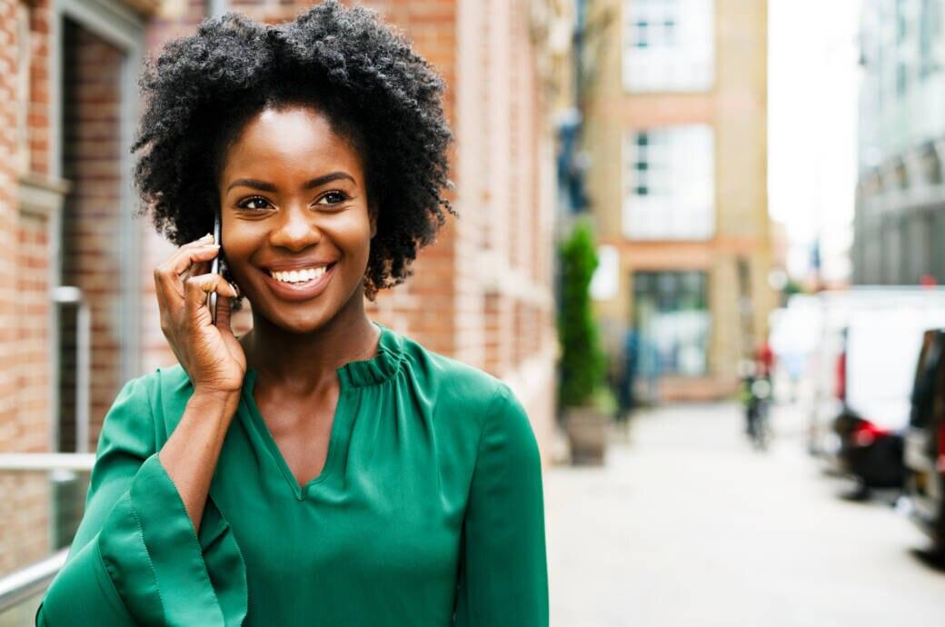Frau telefoniert unterwegs mit dem Smartphone