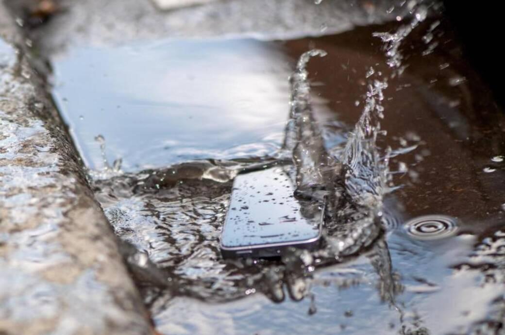 Ein Smartphone liegt in einer Pfütze