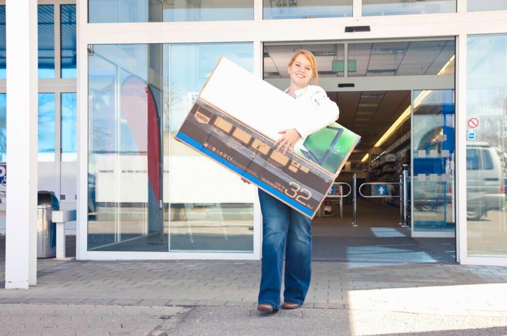 Frau trägt Fernseher aus Elektronik-Markt