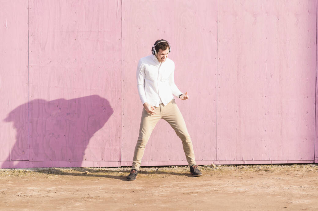 Musik-Streaming-Anbieter im Vergleich: Mann spielt vor rosaner Wand mit Kopfhörern Luftgitarre