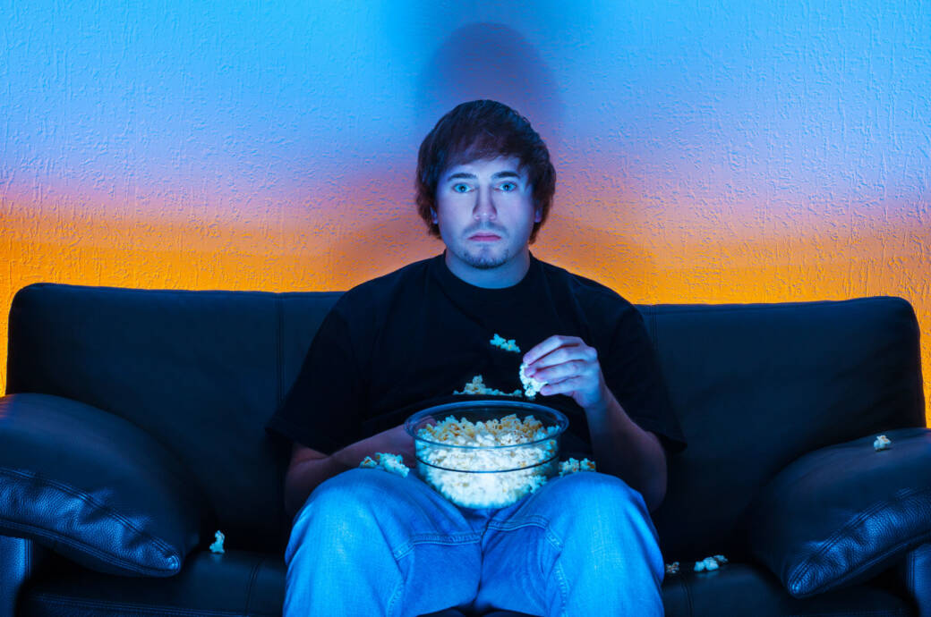 Mann schaut fern und isst dabei Popcorn