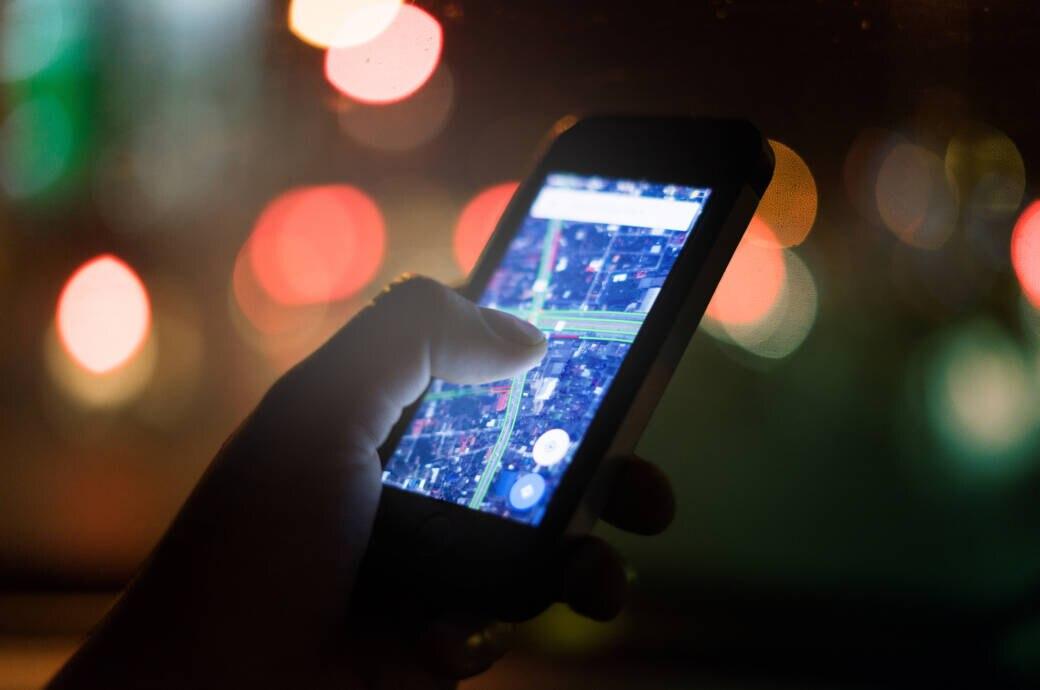 Smartphone mit Netzkarte vor verschwommenem Hintergrund