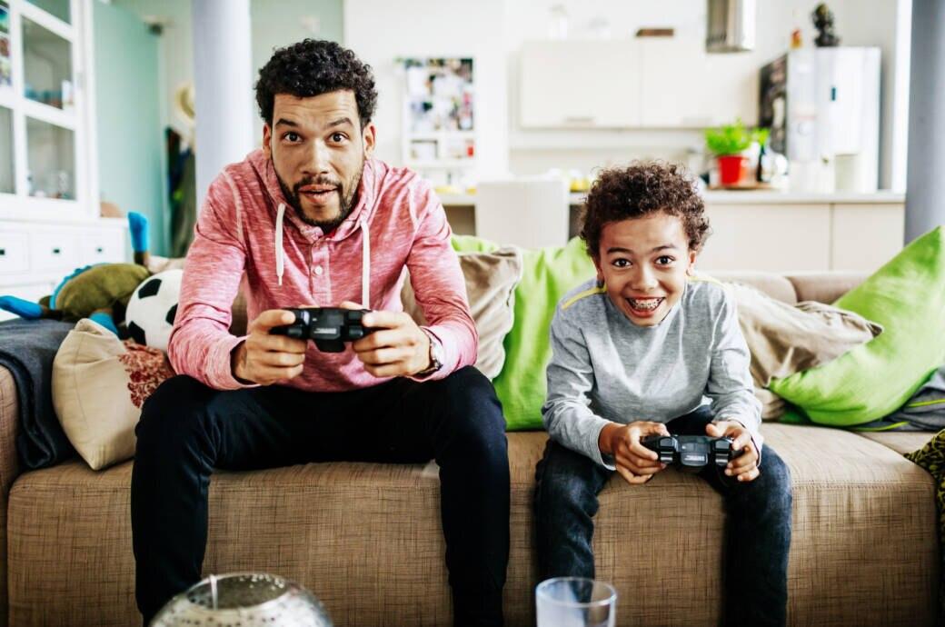 Vater und Sohn spielen mit Spielekonsolen