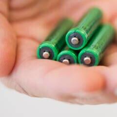 Hand mit vier AAA-Batterien