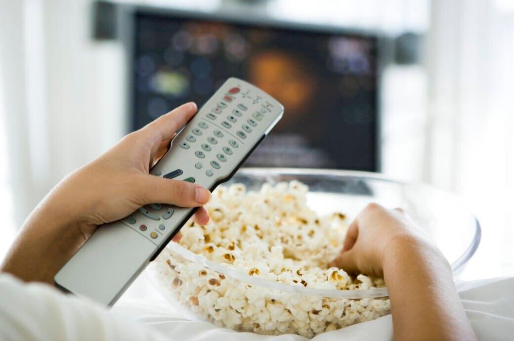 Sky Januar 2020: Person hält Fernbedienung und Popcorn, im Hintergrund ein Fernseher