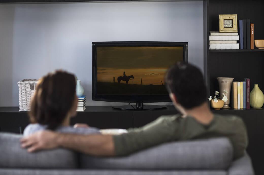 junges Paar auf dem Sofa vor dem Fernseher: Symbolbild Streaming