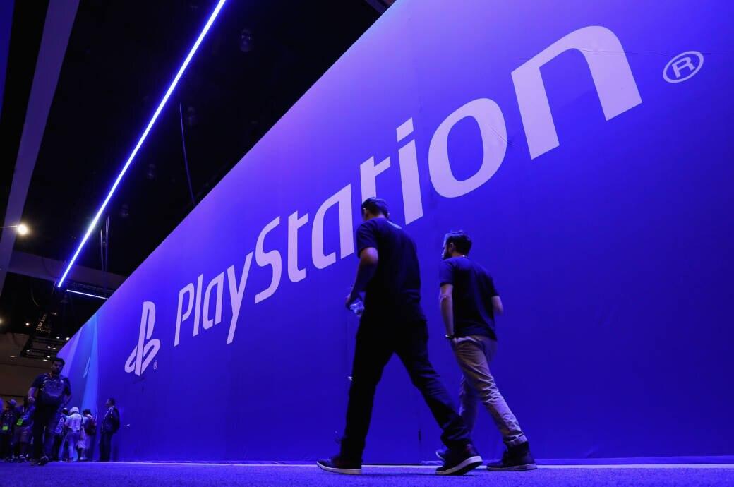 Menschen laufen vor einer großen Wand, auf der Playstation steht