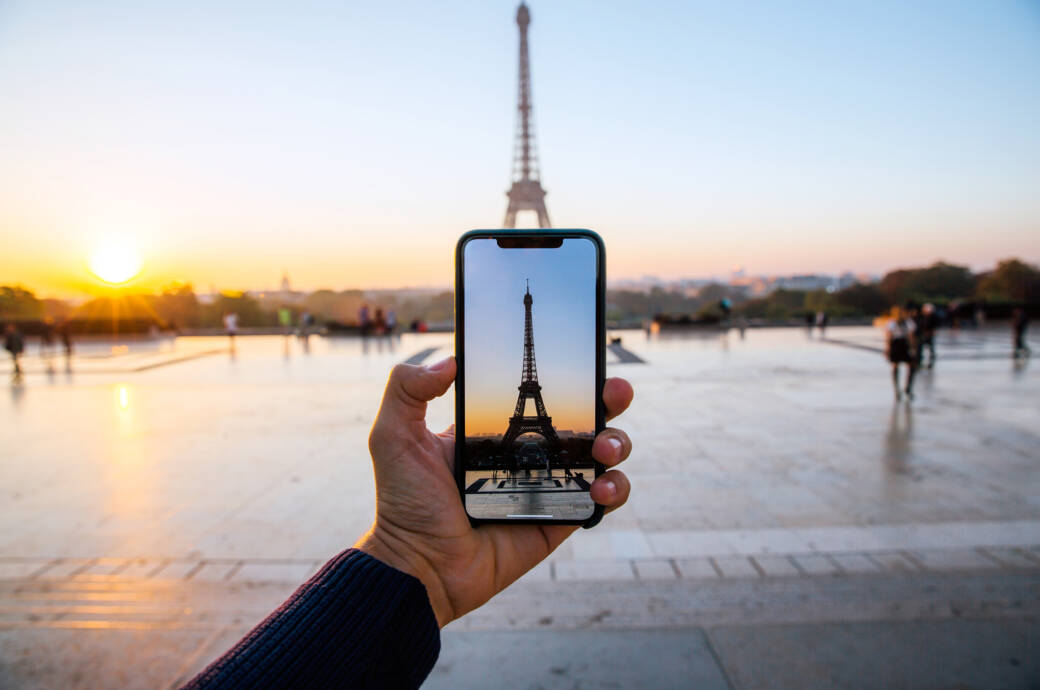 Smartphone-Kamera in einer Hand fotografiert Eiffelturm