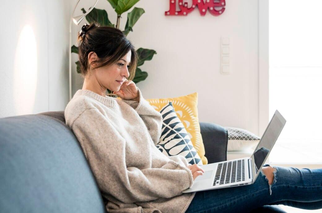 Symbolbild Streaming: Frau sitzt mit ihrem Laptop auf dem Sofa