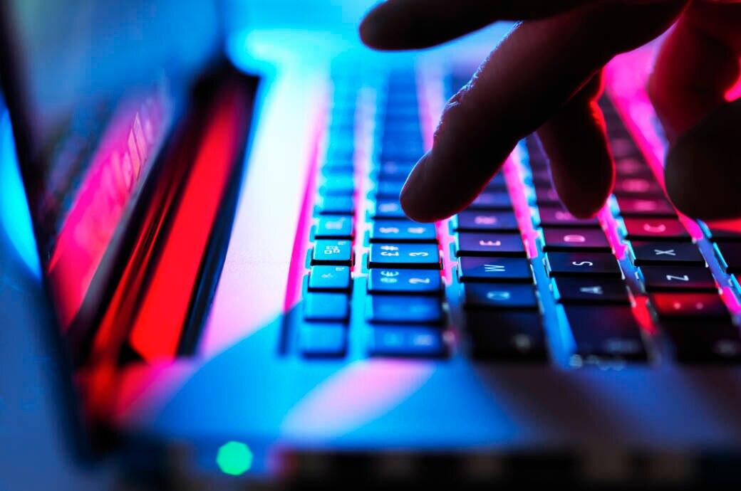 Symbolbild Internetkriminalität Coronavirus: Hand tippt auf einer Computer-Tastatur