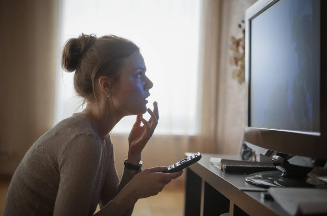 Frau schaut erschrocken auf den Fernseher