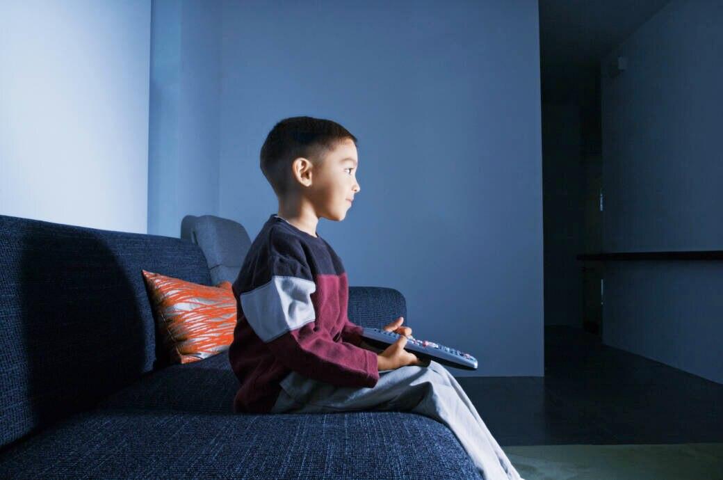Netflix und Amazon Prime Video für Kinder Symbolbild: Ein kleiner Junge sitzt mit der Fernbedienung in der Hand auf dem Sofa