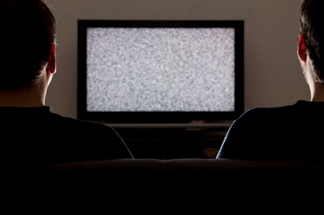 Symbolbild Coronavirus Abschaltung Video-Streaming Schweiz: Zwei Männer schauen auf einen Fernseher ohne Bild