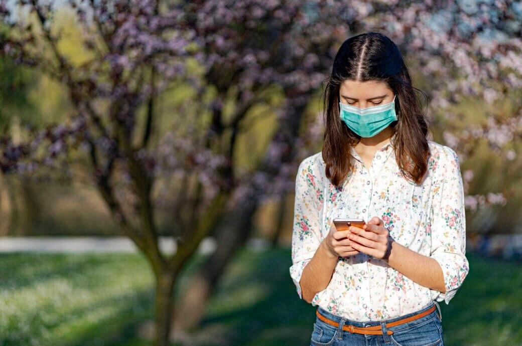 Frau mit Maske steht im Park und schaut aufs Smartphone