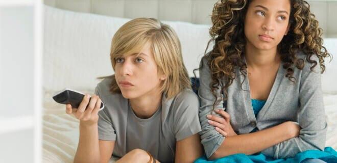 Zwei Teenager traurig vor dem Fernseher