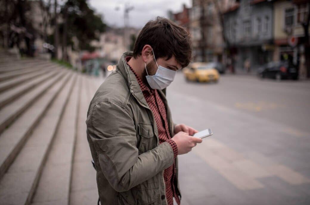 Mann mit Maske und Smartphone auf leerer Straße