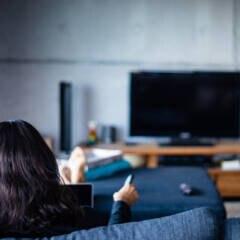 Frau sitzt im Wohnzimmer vor dem Fernseher