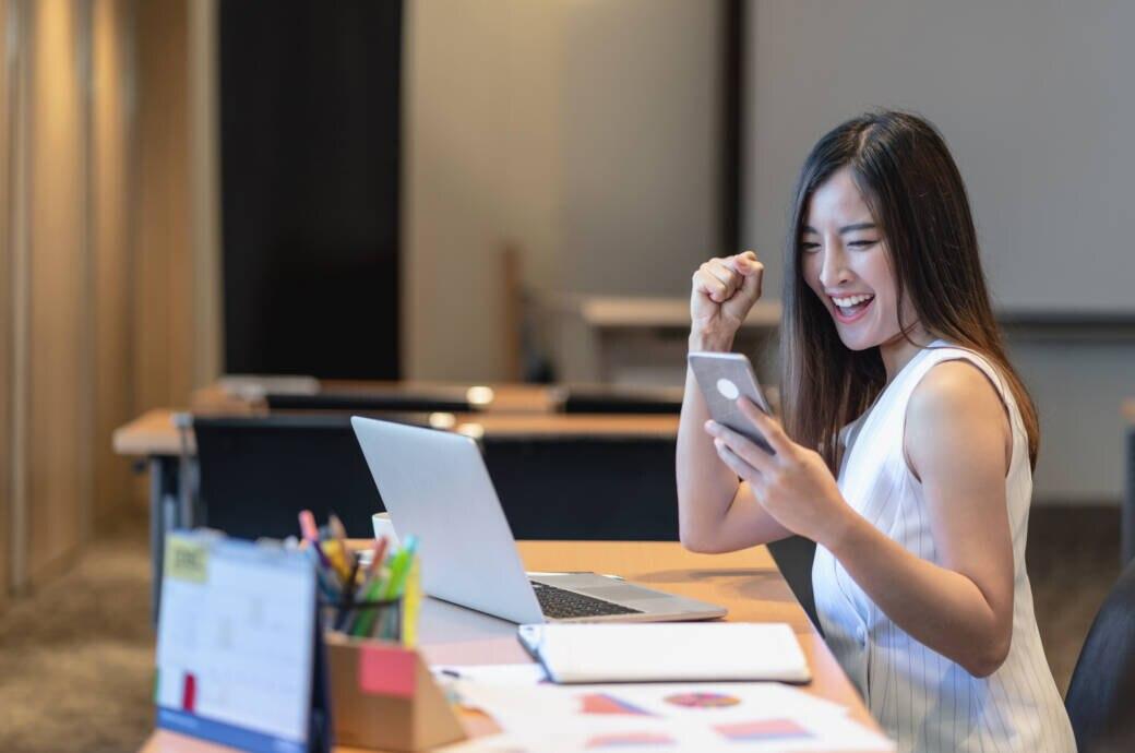 Frau sitzt vor dem Laptop und freut sich