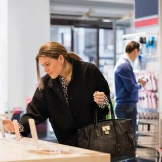 Frau betrachtet Smartphones im Handyshop