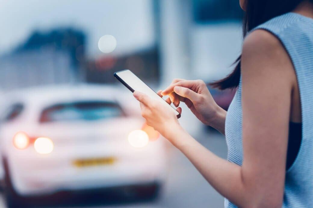 Frau mit Smartphone vor Auto