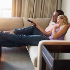 Amazon Prime Video Symbolbild: Mann und Frauen sehen auf dem Sofa fern