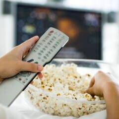 Sky Symbolbild: Mann mit Popcorn vorm Fernseher