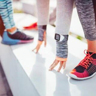 Läuferinnen mit Fitness-Tracker wärmen sich auf