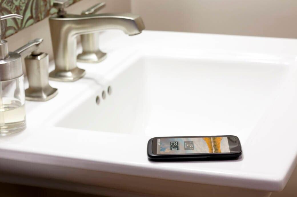 Smartphone liegt auf Waschbeckenrand