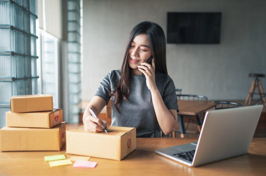 Ebay Kleinanzeigen Alternativen: Junge Frau packt Kartons vor dem Computer