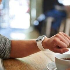 Apple Watch Apps: Apple Watch am Handgelenk neben einer Tasse Kaffee