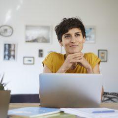 Frau lächelnd vor dem Laptop